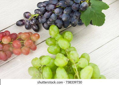 Bunches of fresh ripe blue and rose and green grapes on old wooden rustic white planks