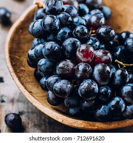 Bunches of fresh ripe red grapes in a wooden bowl on a metal textural surface background. Dark grapes, blue grapes, wine grapes. Autumn Harvest Product Food.  Copy space, closeup