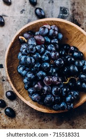 Bunches of fresh ripe red grapes in a wooden bowl on a metal textural surface background. Dark grapes, blue grapes, wine grapes. Copy space, top view
