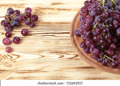 Bunches of fresh ripe red grapes in wicker basket on a wooden textured backdrop. Beautiful background with a branch of berries with copy space.