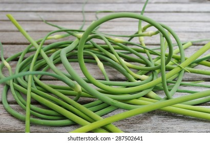 Bunches of freshly picked garlic scape on a wooden table