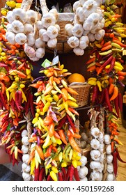 Bunches of garlic and colorful chilli peppers hanging on ropes