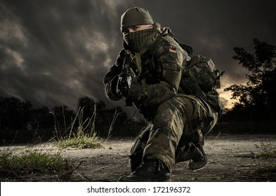 Bundeswehr soldier in a defensive position on the nature background.