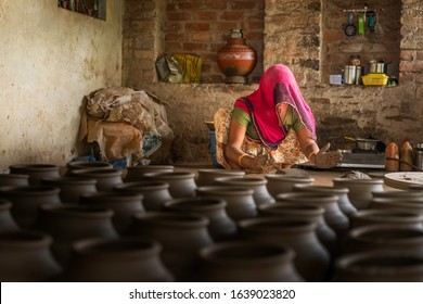 BUNDI, INDIA - OCTOBER 21, 2019:  Woman in traditional colorful clothes kneads wet clay in readiness for the potter in village house on October 21, 2019 near Bundi, Rajasthan, India.