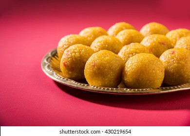 Bundi Laddoo or Motichoor Laddu prepared in pure ghee is a popular sweet item made during festivals (as offering) or weddings in India. Served in a brass plate over moody background. Selective focus