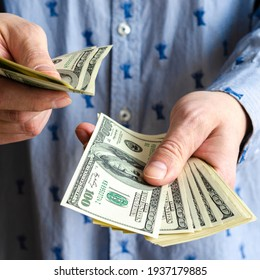 A bundle of American dollars money is rolled up in a hand. Money tied with an elastic band. Roll of American dollars. Human hand. Business and finance. Currency and finance. Cash business.
