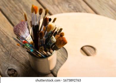 Bündel aus Malpinsel der Künstlerin auf Dottin, leere Palette, rostiges Holz