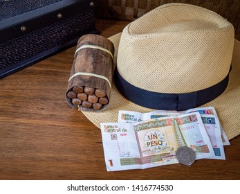 Bundle of authentic cuban cigars sitting on desk with cigar box, panama hat, and cuban peso notes and coin in horizontal with room for copy