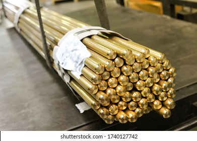 Bundle of bright shiny industrial brass rods in a market tied together with product information slip in close up on the ends