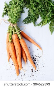 Bundle of carrots with soil over light blue wooden background. Top view