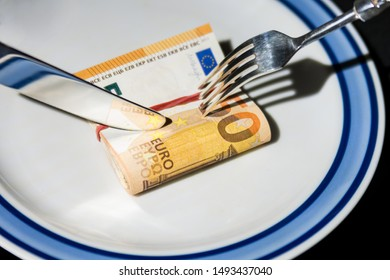 a bundle of fifty euro banknotes is cut with a fork and a knife, a bundle of fifty euro banknotes lies on a white plate with blue stripes