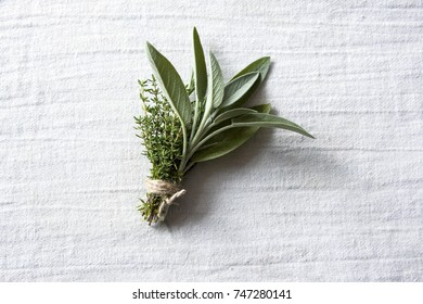 Bundle of Fresh Green Aromatic Herbs Thyme, Rosemary and Sage, Tied with a Thread to be used in Cooking. Close Up Photo on a White Cloth.