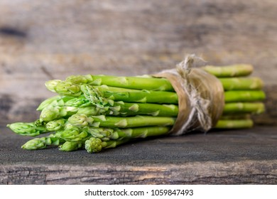 Bundle of fresh green asparagus on a rustic wooden table with copy space. fresh green asparagus on wooden background, top view,vegetable for food health on wood table , selective focus,