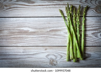 Bundle of fresh green asparagus on a rustic wooden table with copy space, food health, selective focus top view