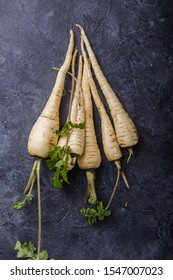 Bundle of fresh organic parsnip  over gray texture background.