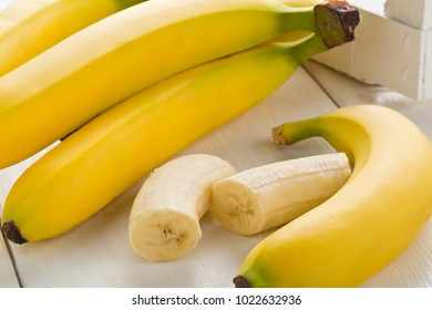 Bundle of fresh, ripe, yellow bananas with sliced banana pieces on white wooden table with white box