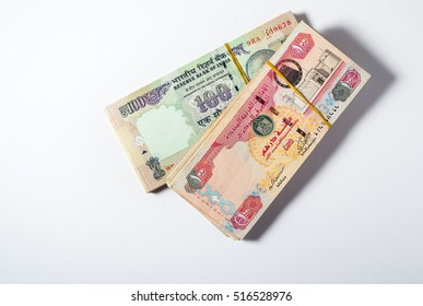 Bundle of Hundred rupee Indian currency notes and UAE dirhams placed side by side on white background. Many expats from UAE send huge remittance to India every day.