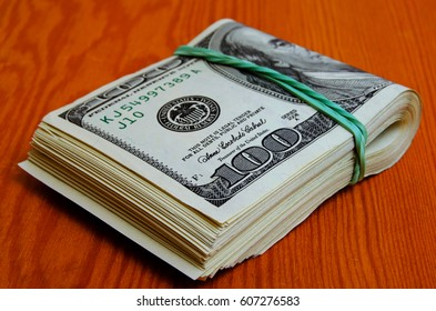Bundle of hundred-dollar bills folded in two, stretched by an elastic band
