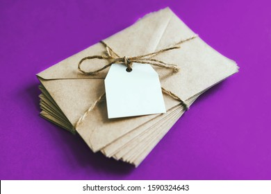 A bundle of letters tied with string on a bow. The white tag is attached to a bundle of envelopes. A stack of letters on a purple background.