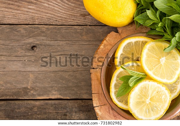 Bundle of mint and slices of lemon on old wooden background. Copy space. Top view. Rustic style.