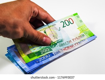 A bundle of money in his hand. Russian rubles. Banknotes of 200 and 2000 rubles.