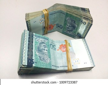 Bundle of money. Malaysia Ringgit (MYR) RM50 with isolated soft grey background.