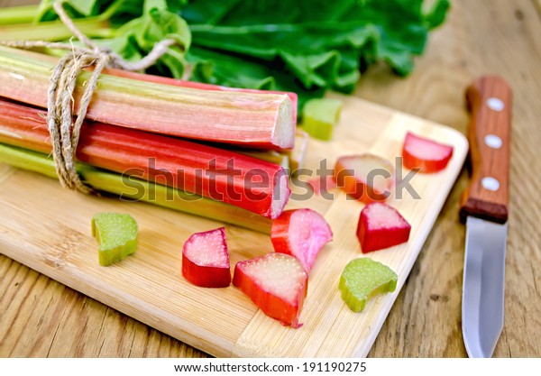 Bundle of stalks, pieces rhubarb, a sheet, a knife on a wooden boards background