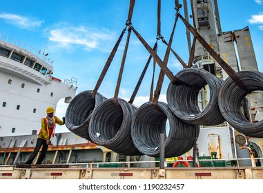 bundle of steel coils being loading discharging by ship crane in port terminal, handle by gang of stevedore labor, shipment cargo in transition from land and sea transport services