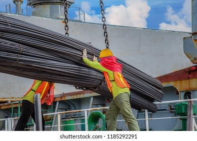 bundle of steel rod being loading discharging in port terminal, handle by gang of stevedore, shipment cargo in transition from land and sea transport services