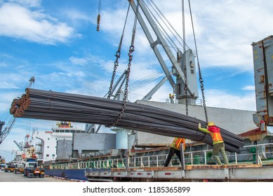 bundle of steel rod being loading discharging in port terminal, handle by gang of stevedore labor , shipment cargo in transition from land and sea transport services