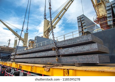 bundle of steel slabs being loading discharging in port terminal, laying onto base of trailer, release unhook,disconnected chain lashing, handle by gang of stevedore labor