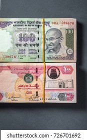 Bundle of UAE dirhams and Indian rupee currency notes placed side by side. Trade, business and remittance between India and United Arab Emirates.