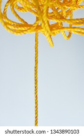 A bundle of yellow nylon rope against white background with a straight portion hanging down.