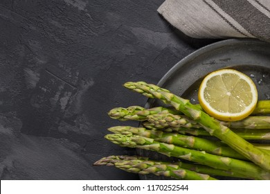 Bundle of young raw uncooked organic green asparagus with sliced lemon and sea salt over black texture background. Top view. Healthy eating