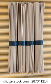 bundles of buckwheat soba noodles on bamboo background