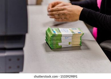 Bundles of € euro banknotes. One hundred euro bundles being counted by a cash counting machine in the treasury department