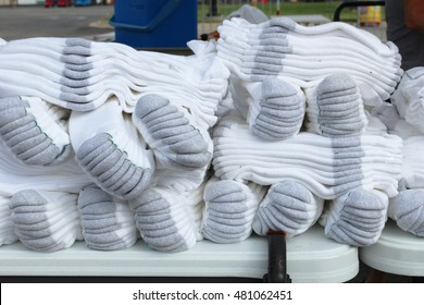 Bundles of white athletic crew socks on a table at an outdoor flea market