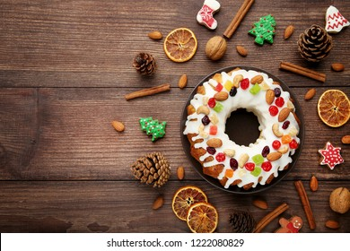 Bundt cake with gingerbread cookies, cinnamon and dried oranges on wooden table