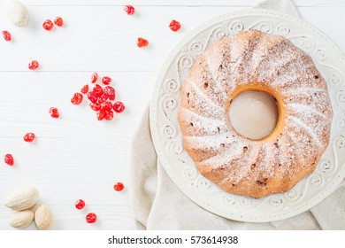 Bundt cake with raisins, dried cherries and sugar powder on a white plate with copy space. Ring cake with icing sugar on white wooden table, top view, flat lay. Festive treat. Festive table setting.