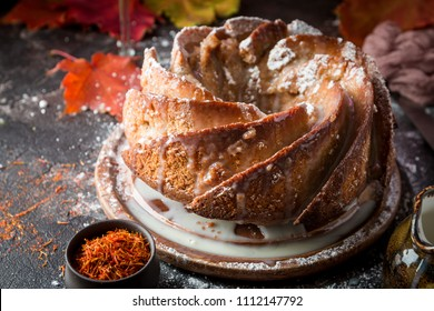 Bundt cake with saffron and rum covered with white glaze on rustic background with autumn decorations