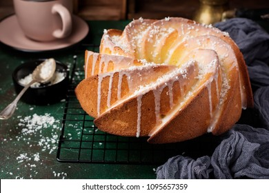 Bundt cake with sugar glaze and coconut on dark green old concrete background. Selective focus.