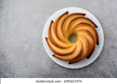 Bundt cake with sugar glaze and coconut on dark grey old concrete background. Selective focus. Top view with copy space.