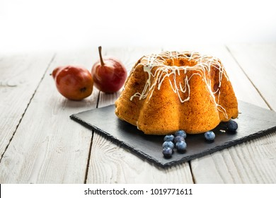 Bundt cake with white topping on the stone plate with blueberries and pear
