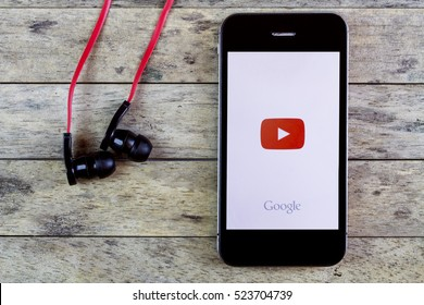 BUNG KAN, THAILAND - AUGUST 25, 2015: smart phone display youtube app with earphones on a wooden table