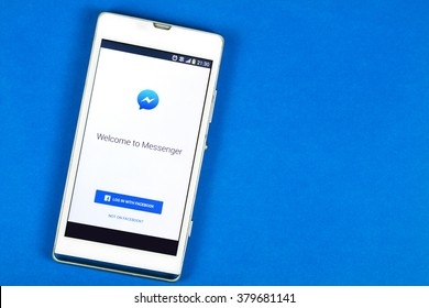 BUNG KAN, THAILAND - FEBRUARY 19, 2016: smart phone display facebook messenger app on blue background, space for caption