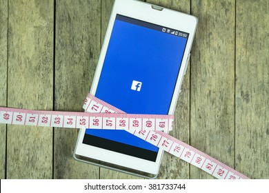 BUNG KAN, THAILAND - FEBRUARY 21 , 2016: smart phone display facebook app and measure tape on office desk