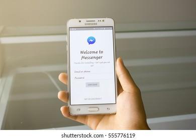 BUNG KAN, THAILAND - JANUARY, 2017: women holding smart phone display facebook messenger app in office