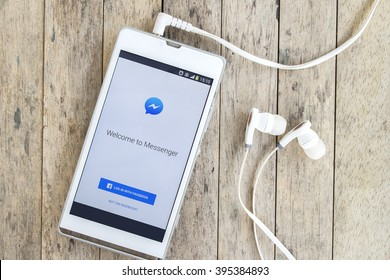 BUNG KAN, THAILAND - MARCH 22, 2016: smart phone display facebook messenger app with earphones on wood background