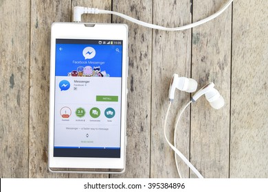 BUNG KAN, THAILAND - MARCH 22, 2016: smart phone display facebook messenger app in google play store with earphones on wood background