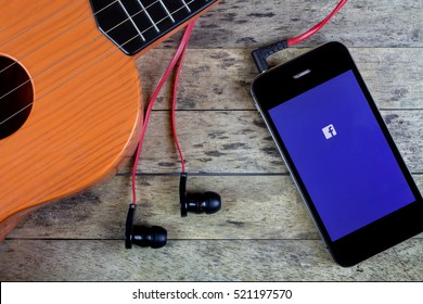 BUNG KAN, THAILAND - OCTOBER 25, 2015: Smart phone and Guitar, earphones and smart phone and facebook app on screen